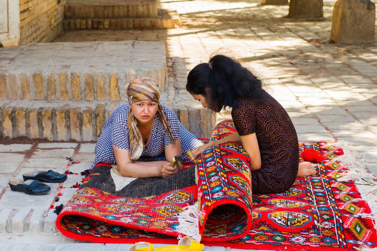 Duas mulheres uzbequestans estão trabalhando em um tapete