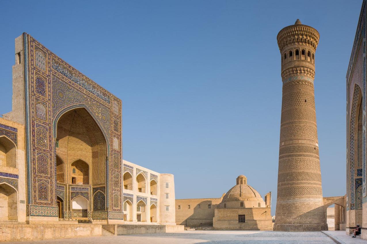 Exterior de Mir-i-árabe Medressa e Kalon Minaret. Dois turistas estão sentados na entrada para Kalon Mosque. Foto tomada em Bukhara, no Uzbequistão.