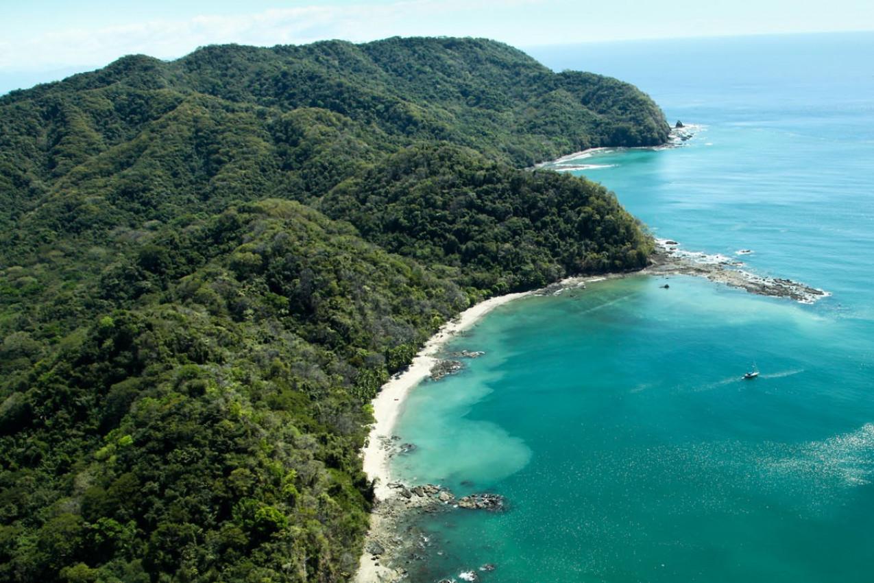 Exuberante floresta montanhas cobertas de esticar-se para o Golfo de Nicoya ao lado da praia rochosa e arenosa de Ballena Bay em Costa Rica