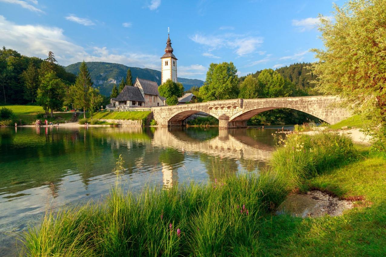 igreja-de-sv-joao-batista-e-uma-ponte-pelo-lago-bohinj-eslovenia