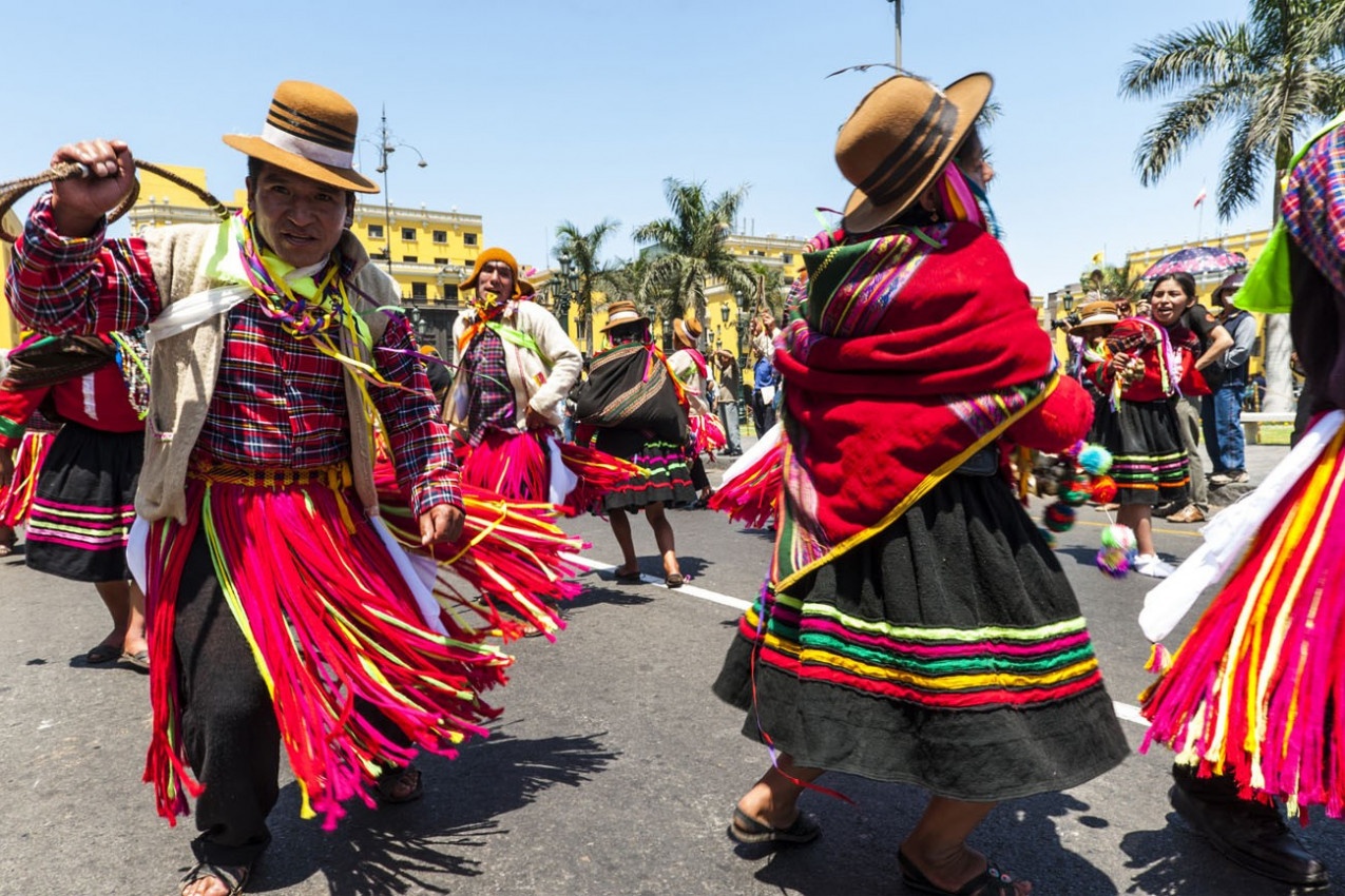 Índios em vestidos tradicionais do Peru dançando na praça Plaza de Armas