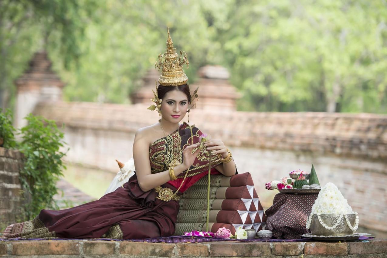 Mulher que desgasta o vestido thai típico com thai fundo do estilo do templo, cultura identidade de Tailândia