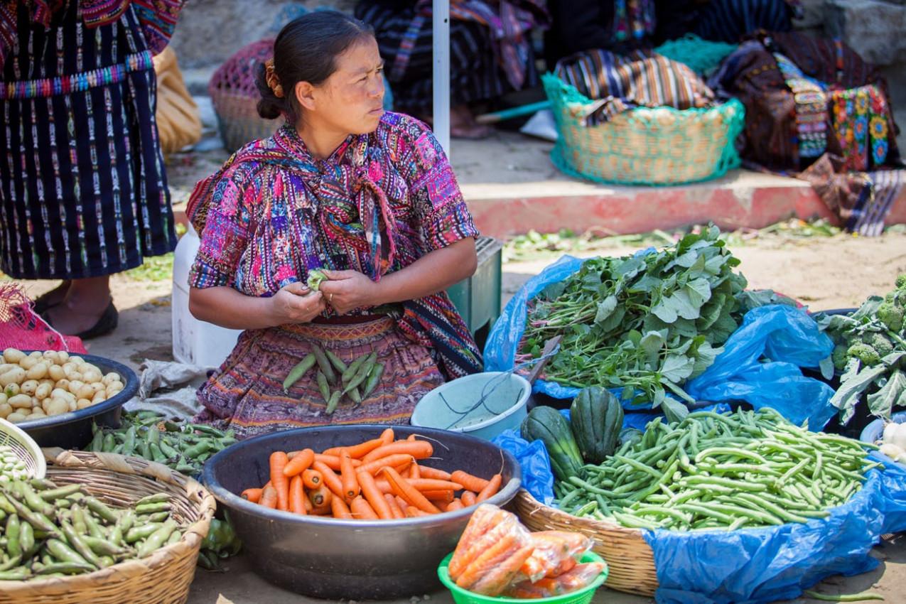 Uma mulher vende vegetais no mercado semanal tradicional em Solola