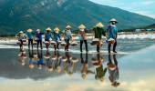 NhaTrang, Vietnam. As mulheres carregam o sal da exploração agrícola de sal para a fábrica.