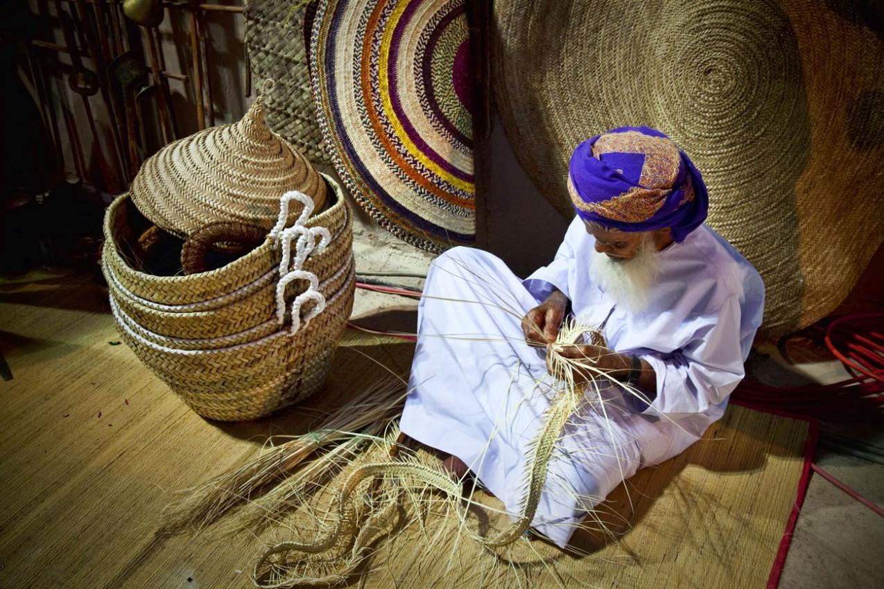 Omani demonstra um do artesanato tradicional do Omã no Festival anual Muscat